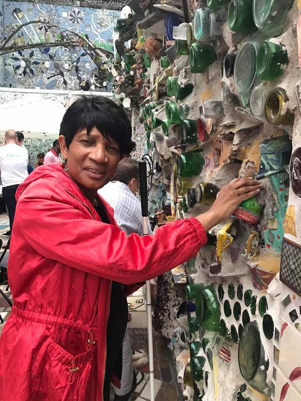 woman touching the Magic Gardens art installation